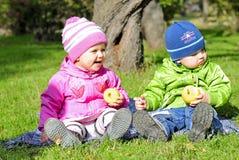 Deux petits enfants s'asseyent sur un effacement vert Photos stock