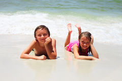 Deux petits enfants se reposant sur la plage et le sourire Images libres de droits