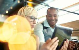 Deux petits entrepreneurs millenial créatifs travaillant sur la stratégie sociale de media utilisant un comprimé numérique tout e Image stock