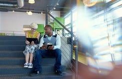 Deux petits entrepreneurs millenial créatifs travaillant sur la stratégie sociale de media utilisant un comprimé numérique tout e Photographie stock libre de droits