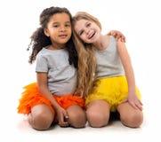 Deux petits fille-amis avec le teint différent se reposant sur le plancher Photographie stock