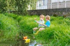 Deux petits frères jouant avec les bateaux de papier par une rivière Image stock