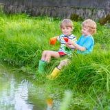 Deux petits frères jouant avec les bateaux de papier par une rivière Images stock