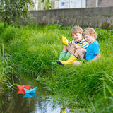 Deux petits frères jouant avec les bateaux de papier par une rivière Photographie stock