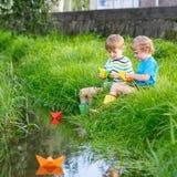 Deux petits frères jouant avec les bateaux de papier par une rivière Photo libre de droits