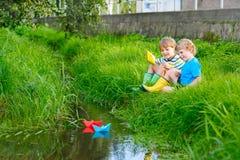 Deux petits frères jouant avec les bateaux de papier par une rivière Images libres de droits