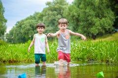 Deux petits frères jouant avec les bateaux de papier par une rivière le jour chaud et ensoleillé d'été Photo libre de droits