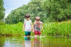 Deux petits frères jouant avec les bateaux de papier par une rivière le jour chaud et ensoleillé d'été Photographie stock