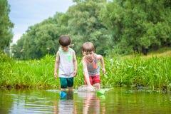 Deux petits frères jouant avec les bateaux de papier par une rivière le jour chaud et ensoleillé d'été Images stock