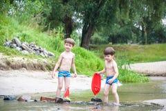 Deux petits frères jouant avec les bateaux de papier par une rivière le jour chaud et ensoleillé d'été Photos stock