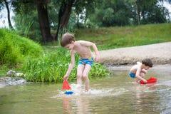 Deux petits frères jouant avec les bateaux de papier par une rivière le jour chaud et ensoleillé d'été Photo stock