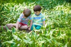 Deux petits frères jouant avec les bateaux de papier par une rivière le jour chaud et ensoleillé d'été Image stock