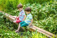 Deux petits frères jouant avec les bateaux de papier par une rivière le jour chaud et ensoleillé d'été Photos libres de droits
