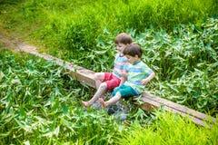 Deux petits frères jouant avec les bateaux de papier par une rivière le jour chaud et ensoleillé d'été Images libres de droits