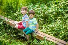 Deux petits frères jouant avec les bateaux de papier par une rivière le jour chaud et ensoleillé d'été Image libre de droits
