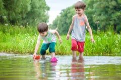 Deux petits frères jouant avec les bateaux de papier par une rivière sur chaud Photo libre de droits