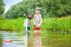 Deux petits frères jouant avec les bateaux de papier par une rivière sur chaud Photos libres de droits