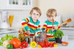 Deux petits frères mignons faisant cuire la soupe et le repas italiens avec des fres Photographie stock libre de droits