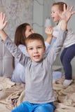 Deux petits frères ont l'amusement avec leur jeune mère habillée dans le pyjama bleu-clair sur le lit avec la couverture beige da image libre de droits