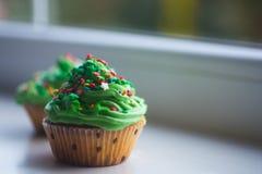 Deux petits gâteaux de nouvelle année avec le dessus vert crémeux avec les étoiles colorées et arrose en journée photo stock