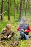 Deux petits garçons allumant un feu dans la région boisée Image libre de droits