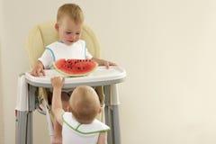 Deux petits garçons avec les poils blonds mangeant la pastèque rouge images stock