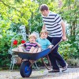 Deux petits garçons ayant l'amusement dans la brouette poussant par le père Image libre de droits