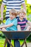 Deux petits garçons ayant l'amusement dans la brouette poussant par le père Photographie stock libre de droits