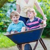 Deux petits garçons ayant l'amusement dans une brouette poussant par la mère Photos stock