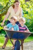 Deux petits garçons ayant l'amusement dans une brouette poussant par la mère Photos libres de droits