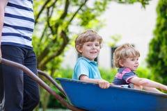 Deux petits garçons ayant l'amusement dans une brouette poussant par le père dedans photographie stock libre de droits