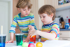 Deux petits garçons blonds d'enfant colorant des oeufs pour des vacances de Pâques Image libre de droits