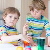 Deux petits garçons blonds d'enfant colorant des oeufs pour des vacances de Pâques Photos stock