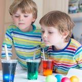Deux petits garçons blonds d'enfant colorant des oeufs pour des vacances de Pâques Image stock