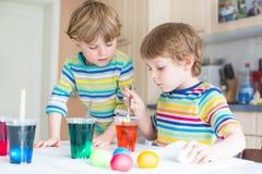 Deux petits garçons blonds d'enfant colorant des oeufs pour Pâques Images libres de droits