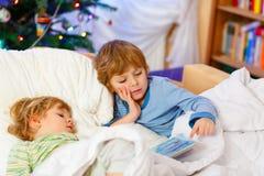 Deux petits garçons blonds d'enfant de mêmes parents lisant un livre sur Noël Image libre de droits