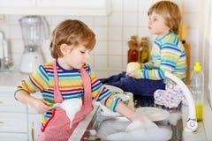 Deux petits garçons blonds d'enfant lavant des plats dans la cuisine domestique Image libre de droits