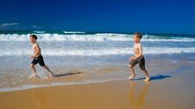 Deux petits garçons courant sur une plage sablonneuse le jour ensoleillé banque de vidéos