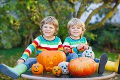 Deux petits garçons d'amis faisant la cric-o-lanterne pour Halloween dans a Photographie stock