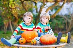 Deux petits garçons d'amis faisant la cric-o-lanterne pour Halloween dans a Photos stock