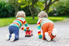 Deux petits garçons d'amis jouant avec l'autobus scolaire rouge Images libres de droits