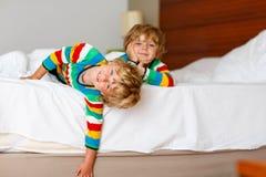 Deux petits garçons d'enfant d'enfant de mêmes parents ayant l'amusement dans le lit Image libre de droits