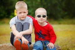 Deux petits garçons d'enfant de mêmes parents étreignant et ayant dehors Frères Photographie stock