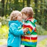 Deux petits garçons d'enfant de mêmes parents dans les imperméables colorés et la marche de bottes Photo stock