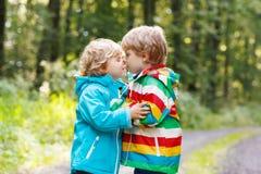 Deux petits garçons d'enfant de mêmes parents dans les imperméables colorés et la marche de bottes Images libres de droits