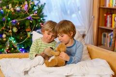 Deux petits garçons d'enfant de mêmes parents jouant des jouets sur Noël Photos libres de droits