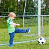 Deux petits garçons d'enfant de mêmes parents jouant le football et le football sur le champ Images stock