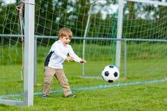 Deux petits garçons d'enfant de mêmes parents jouant le football et le football sur le champ Photographie stock
