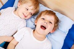 Deux petits garçons d'enfant en bas âge ayant l'amusement dans le lit Images stock
