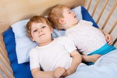 Deux petits garçons d'enfant en bas âge ayant l'amusement dans le lit Image libre de droits